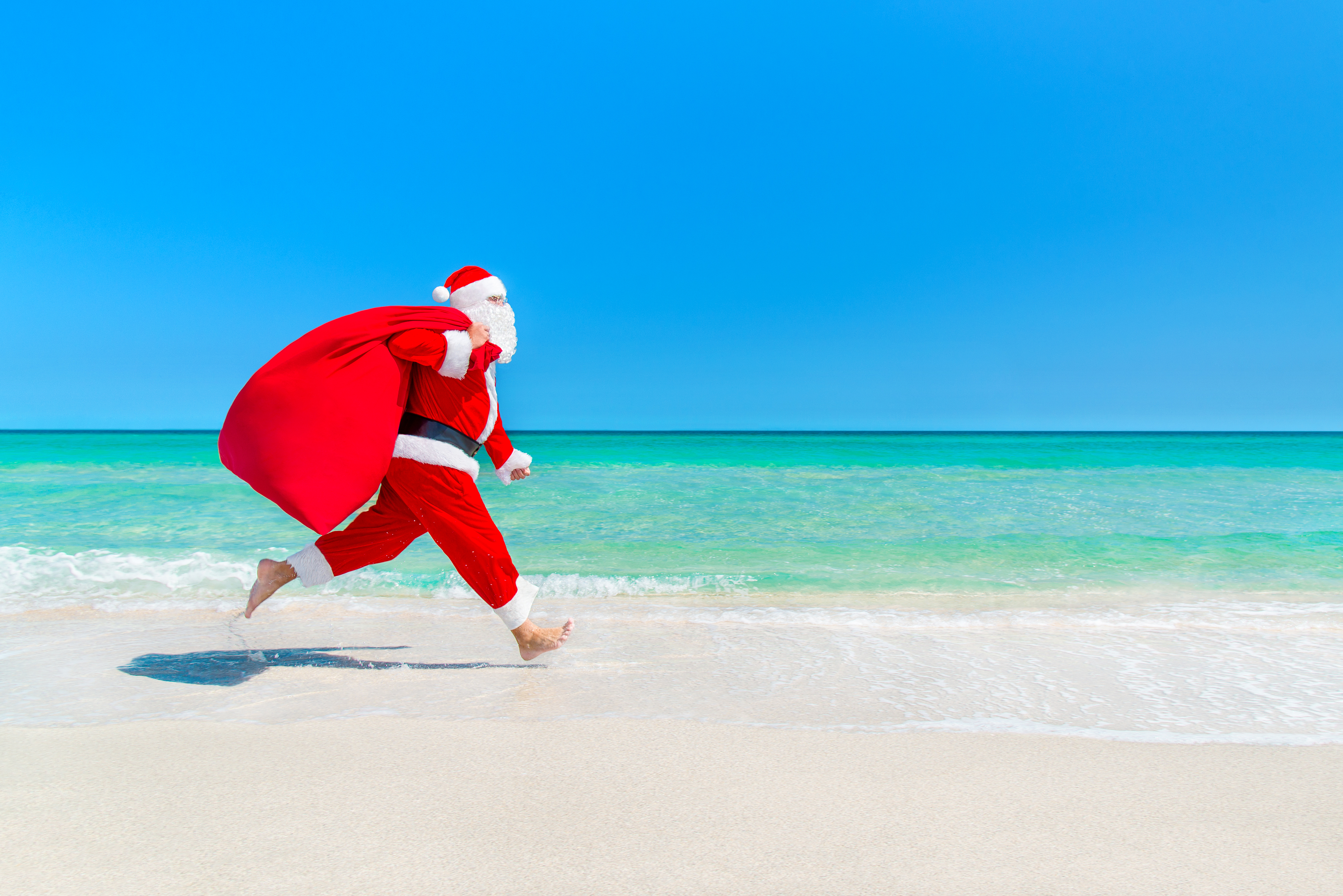 Christmas Santa Claus running with big sack full of gifts hurry on present it for children along ocean tropical sandy beach - xmas travel vacation discounts and travel agencies price reductions concept