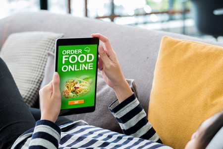 Order Food Online Concpet.woman Lying Down On Sofa Using Tablet See Restaurant Menu Online At Home.digital Technology Lifestyle.