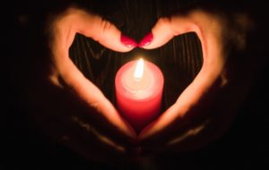 Heart Shaped Female Hands Around Burning Red Candle