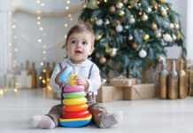 The Kid, Sitting On The Floor Near A Smart Christmas Tree, Collects A Multicolored Pyramid.
