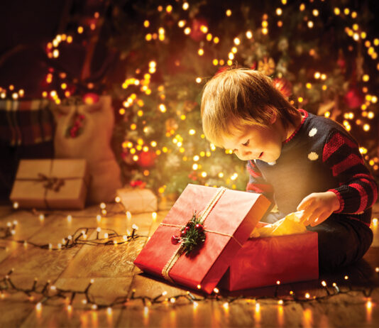 Christmas Child Open Present Gift, Happy Baby Boy Looking To Magic Light In Box, Kid And Xmas Tree