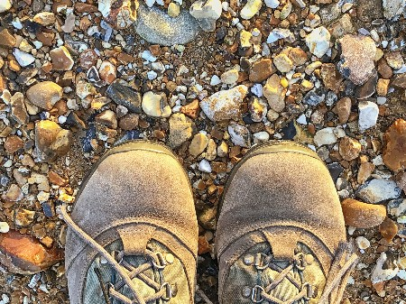 Person,wearing,walking,boots,standing,on,a,pebble,beach,with